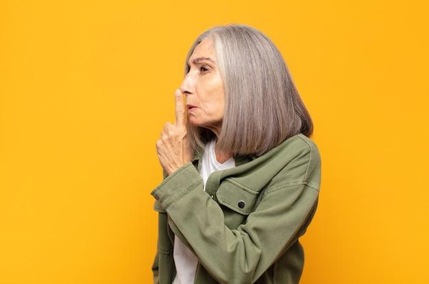 Женщина среднего возраста просит тишины и тишины, жестикулирует пальцем перед ртом, говорит тсс или держит в секрете