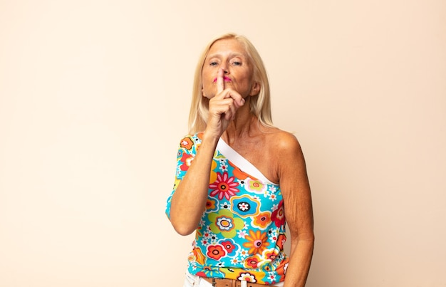 Middle age woman asking for silence and quiet, gesturing with finger in front of mouth, saying shh or keeping a secret
