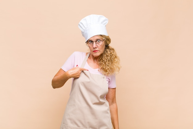 Middle age woman baker feeling confused, puzzled and insecure, pointing to self wondering and asking who, me?