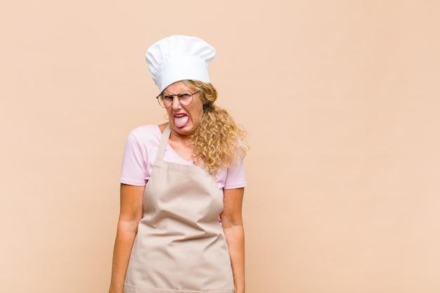 Женщина-пекарь среднего возраста чувствует отвращение и раздражение, высовывает язык, не любит что-то противное и противное