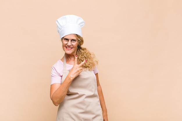 Женщина-пекарь среднего возраста чувствует себя счастливой, позитивной и успешной, с рукой делает v-образную форму на груди, показывая победу или мир