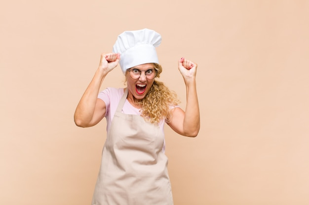 Женщина-пекарь среднего возраста чувствует себя счастливой, удивленной и гордой, кричит и празднует успех с широкой улыбкой