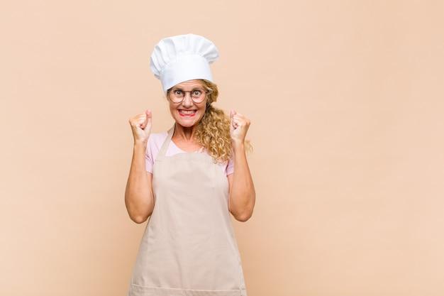 Женщина-пекарь среднего возраста чувствует себя потрясенной, взволнованной и счастливой, смеется и празднует успех, говоря: