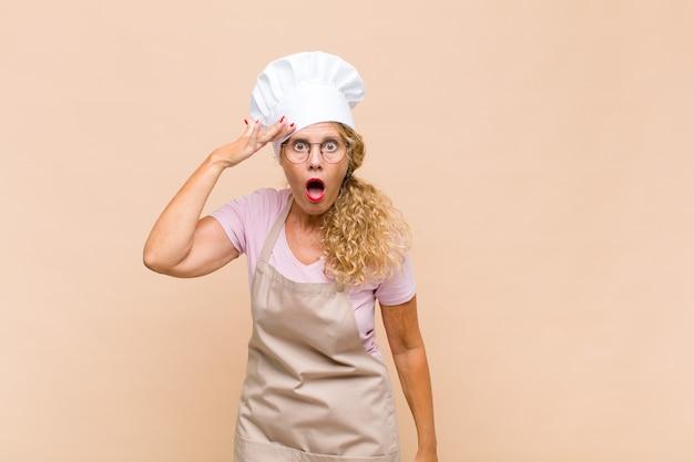 Женщина-пекарь среднего возраста выглядит счастливой, удивленной и удивленной, улыбается и понимает удивительные и невероятно хорошие новости