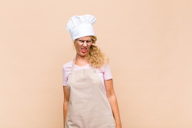 ショックを受けた、怒った、イライラした、または失望した、口を開けて激怒している中年の女性パン屋