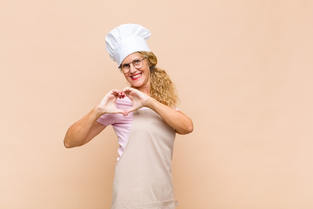 Middle age woman baker smiling and feeling happy, cute, romantic and in love, making heart shape with both hands