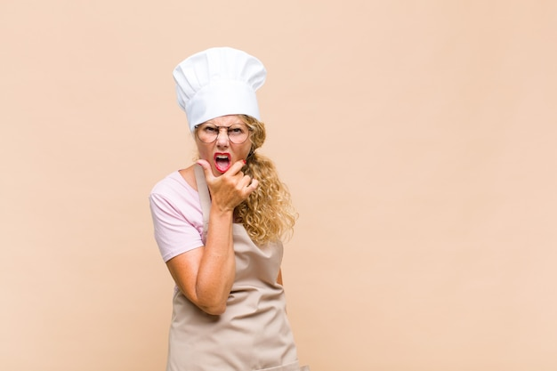 Middle age woman baker with mouth and eyes wide open and hand on chin, feeling unpleasantly shocked, saying what or wow