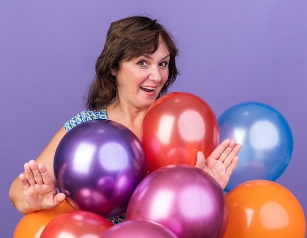 Middle age woman bunch of colorful balloons  happy and surprised
