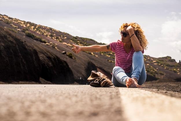 中年女性の白人の人々は、壊れた靴と裸足のトレッキングライフスタイルで道路に座ってヒッチハイキングをします。女性と世界中の自由な生活のための旅行のコンセプト-放浪者と旅行者