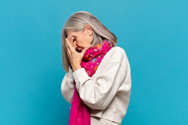Middle age woman covering eyes with hands with a sad, frustrated look of despair, crying, side view