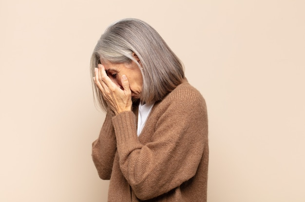 Middle age woman covering eyes with hands with a sad, frustrated look of despair