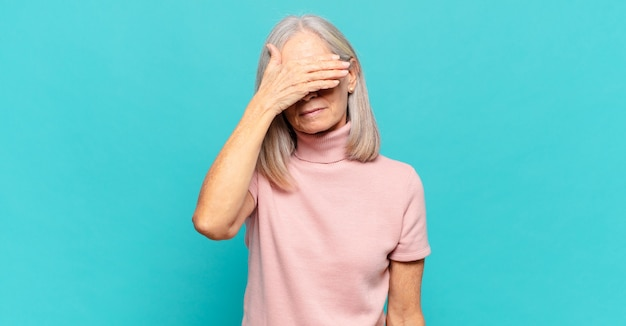 Middle age woman covering eyes with one hand feeling scared or anxious, wondering or blindly waiting for a surprise