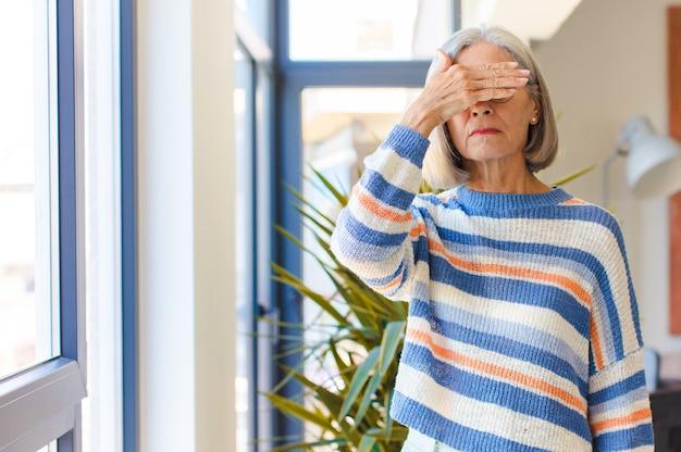 片手で目を覆っている中年女性が怖い、不安、不思議、または盲目的に驚きを待っている