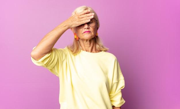 한 손으로 눈을 가리는 중년 여성은 무서워하거나 불안해하거나 궁금해하거나 맹목적으로 놀라움을 기다리고 있습니다.