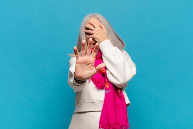 Женщина среднего возраста закрывает лицо рукой и поднимает другую руку вперед, чтобы остановить камеру, отказываясь от фотографий или изображений