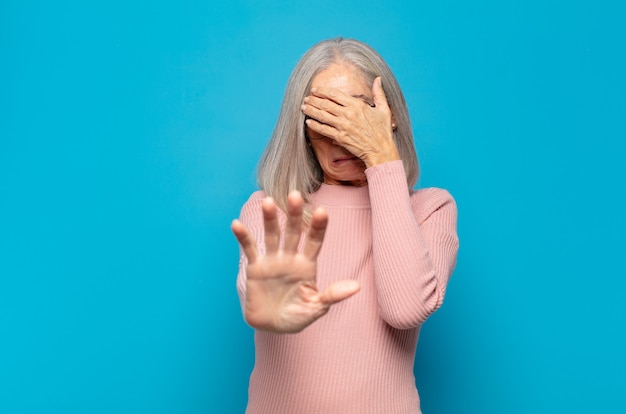 Женщина среднего возраста, закрывающая лицо рукой и поднимающая другую руку вперед, чтобы остановиться, отказываясь от фотографий или изображений