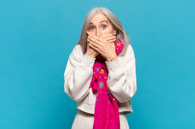 Женщина среднего возраста закрывает рот руками с шокированным, удивленным выражением лица, хранит секрет или говорит: ой