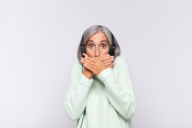 Middle age woman covering mouth with hands with a shocked isolated