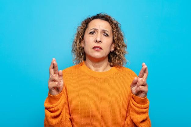 Женщина среднего возраста тревожно скрещивает пальцы и с тревогой надеется на удачу