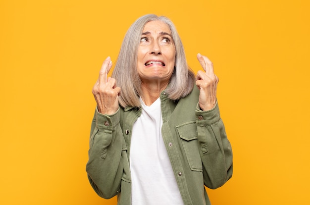 Middle age woman crossing fingers anxiously and hoping for good luck with a worried look