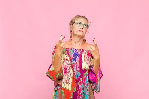 Женщина среднего возраста с тревогой скрещивает пальцы