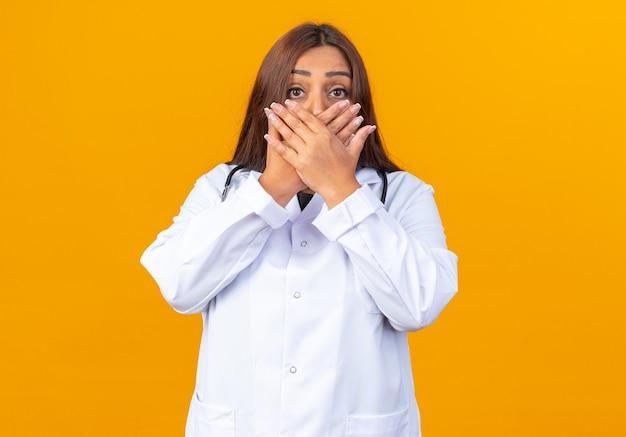청진기가 주황색 벽 위에 서 있는 손으로 입을 가리고 충격을 받는 흰색 코트를 입은 중년 여성 의사