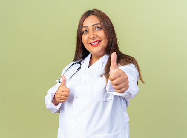 緑の壁の上に立って親指を元気に見せて幸せで前向きな笑顔の聴診器と白衣を着た中年女性医師