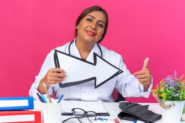 흰색 코트를 입은 중년 여성 의사는 청진기를 들고 화살표를 들고 분홍색으로 사무실 폴더가 있는 탁자에 앉아 엄지손가락을 치켜들며 자신감 있게 웃고 있습니다.