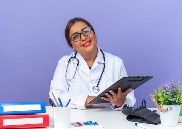青い壁の上のテーブルに座って幸せそうな顔に笑顔でクリップボードを保持聴診器と白衣を着た中年女性医師