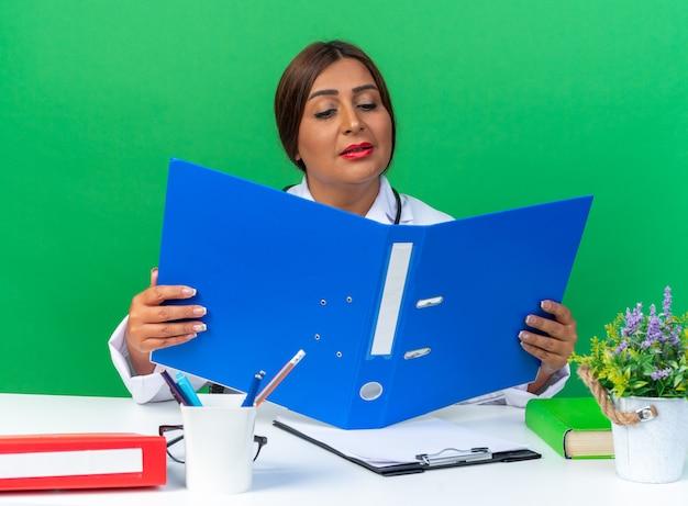 흰색 코트를 입은 중년 여성 의사가 청진기를 들고 열린 사무실 폴더를 보고 녹색 테이블에 앉아 흥미롭게 보고 있습니다.