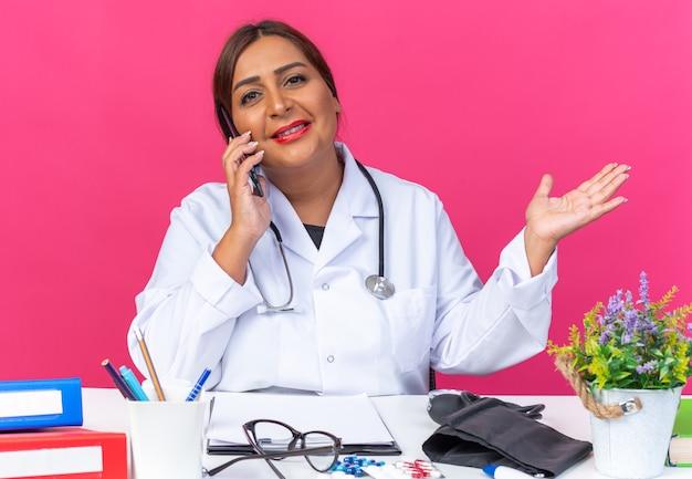 흰색 코트를 입은 중년 여성 의사는 분홍색 배경 위에 사무실 폴더가 있는 테이블에 앉아 휴대전화로 통화하면서 자신감 있게 웃고 있는 청진기를 들고 있다