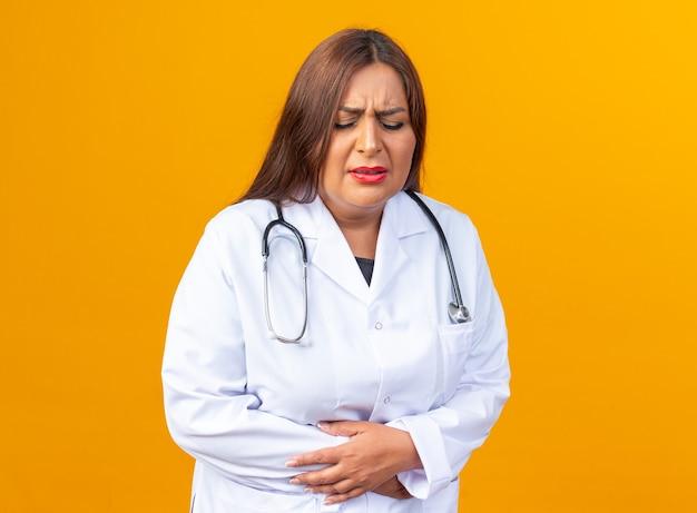 흰색 코트를 입은 중년 여성 의사, 청진기가 주황색 벽 위에 서 있는 고통으로 고통받는 배를 만지고 있는 몸이 좋지 않은 것처럼 보입니다.