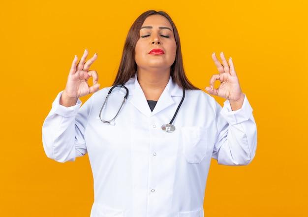 Женщина-врач среднего возраста в белом халате со стетоскопом расслабляет, делая жест медитации с закрытыми глазами