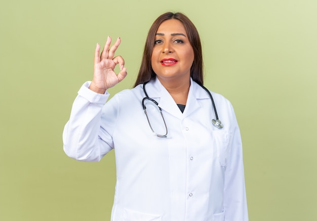 흰색 코트를 입은 중년 여성 의사와 청진기가 녹색 위에 서 있는 확인 표시를 하고 자신감 있게 웃고 있습니다.