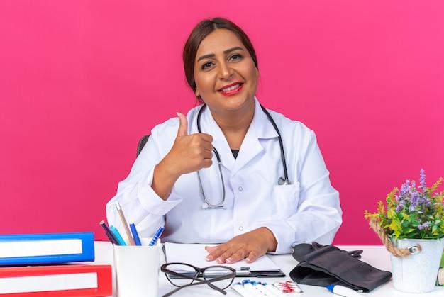 Женщина-врач среднего возраста в белом халате со стетоскопом, уверенно улыбаясь, показывает палец вверх, сидя за столом с офисными папками на розовом