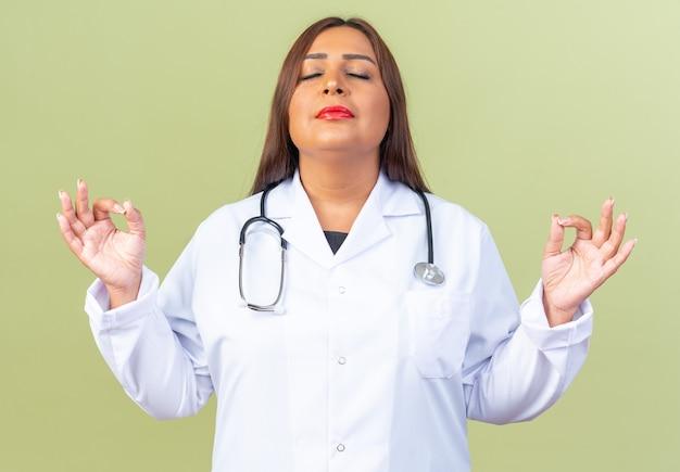 Женщина-врач среднего возраста в белом халате со стетоскопом пытается расслабиться с закрытыми глазами, делая жест медитации макин, стоя на зеленом