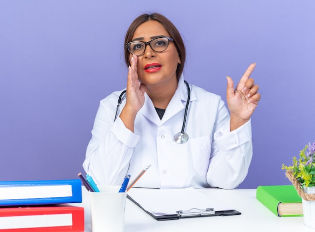青い壁の上のテーブルに座っている側に指で指している口の近くの手で秘密を告げる眼鏡をかけた聴診器と白衣を着た中年の女性医師