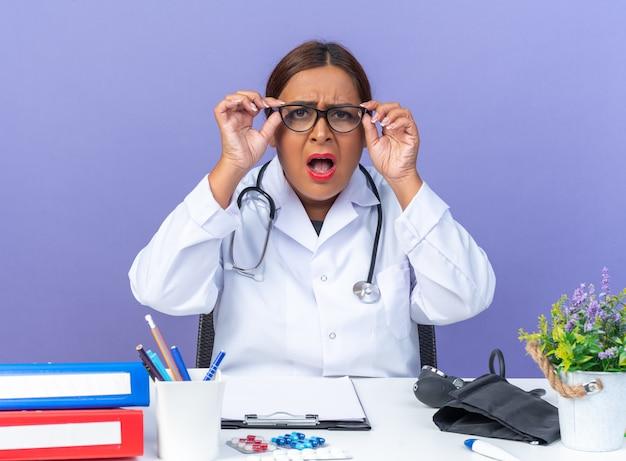 青い壁の上のテーブルに座って混乱し、欲求不満の怒っている顔と眼鏡をかけて聴診器と白衣を着た中年女性医師