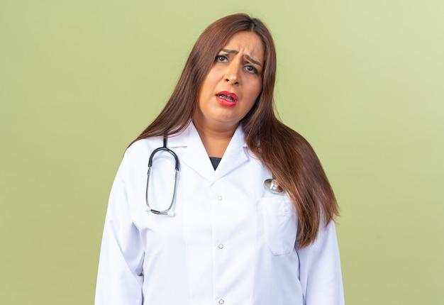 Medico della donna di mezza età in camice bianco con lo stetoscopio che è confuso e molto ansioso in piedi sul verde