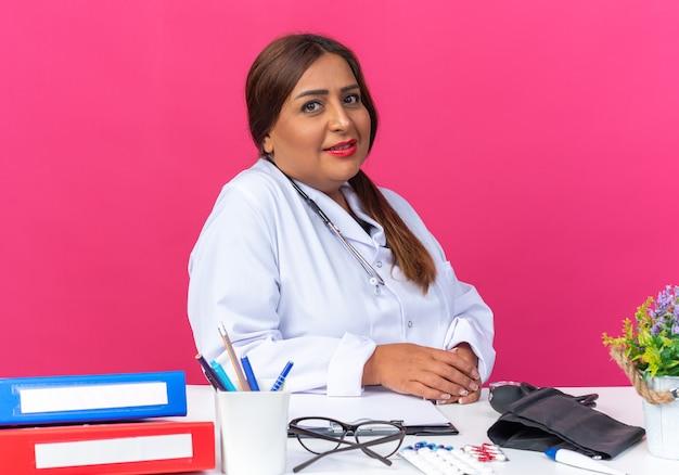 Medico donna di mezza età in camice bianco con stetoscopio felice e fiducioso seduto al tavolo con cartelle da ufficio su muro rosa