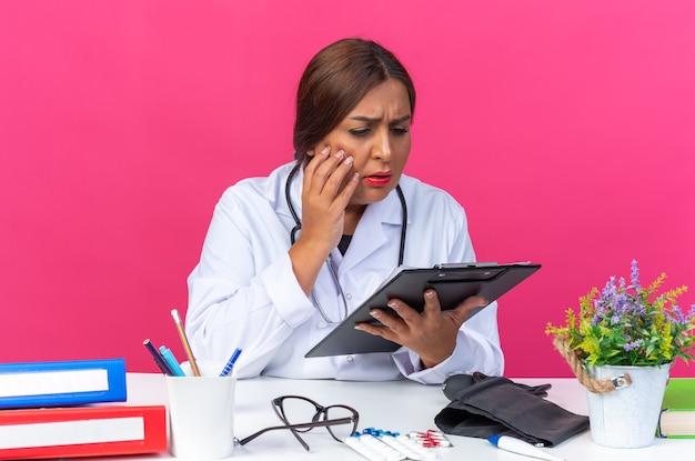 Medico della donna di mezza età in camice bianco con lo stetoscopio che tiene appunti guardandolo con faccia seria seduto al tavolo con cartelle per ufficio su sfondo rosa