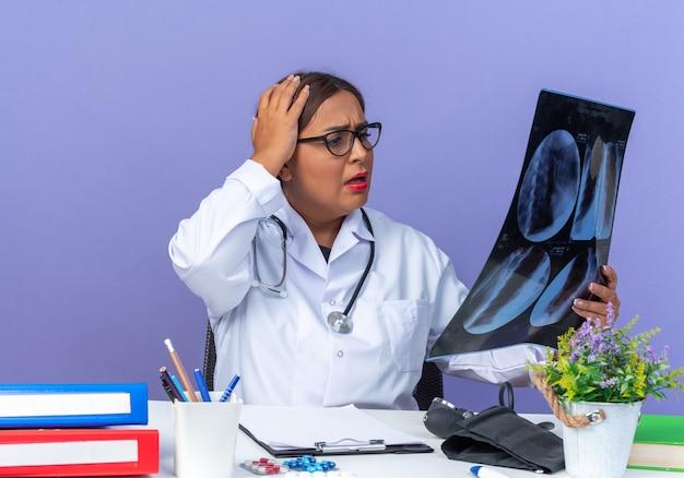 Medico donna di mezza età in camice bianco con stetoscopio che tiene raggi x guardandolo con espressione confusa con la mano sulla testa seduta al tavolo sul muro blu
