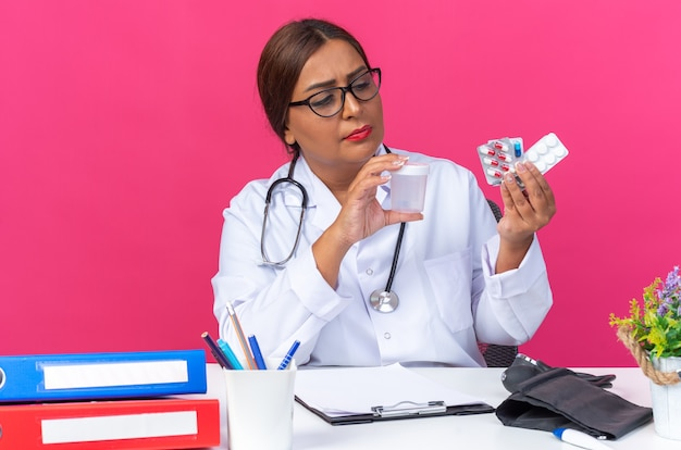 Middle age woman doctor in white coat with stethoscope holing different pills and test jar looking at them serious face sitting at the table over pink wall