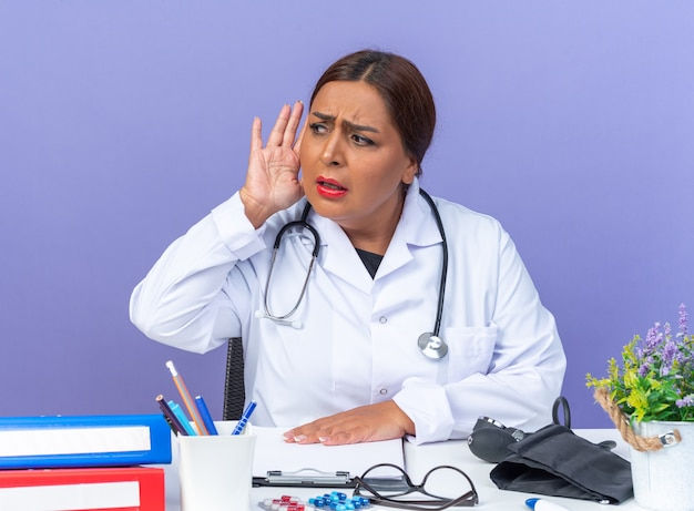 Middle age woman doctor in white coat with stethoscope looking aside with hand over ear trying to listen sitting at the table over blue wall