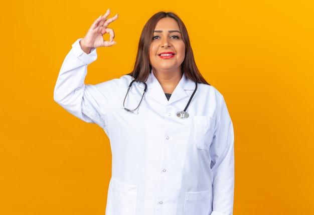 Medico della donna di mezza età in camice bianco con lo stetoscopio che sembra felice e positivo sorridente fiducioso che mostra segno giusto