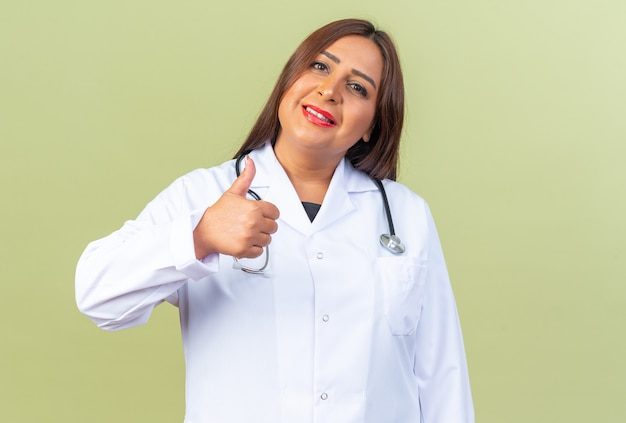 Middle age woman doctor in white coat with stethoscope looking smiling confident showing thumbs up