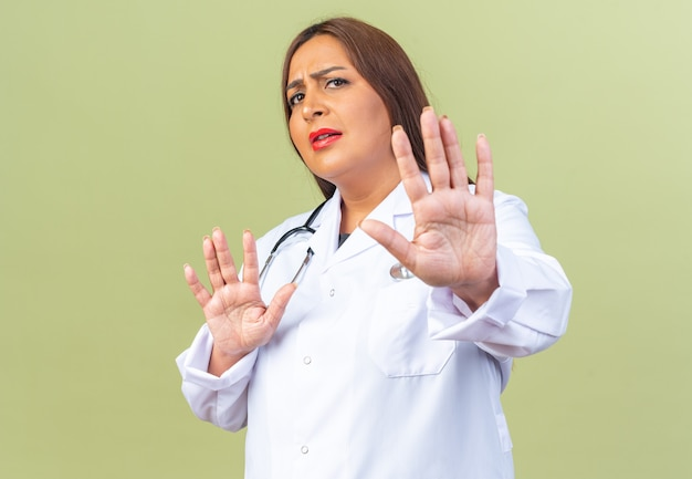 Middle age woman doctor in white coat with stethoscope looking worried making defense gesture with hands standing on green