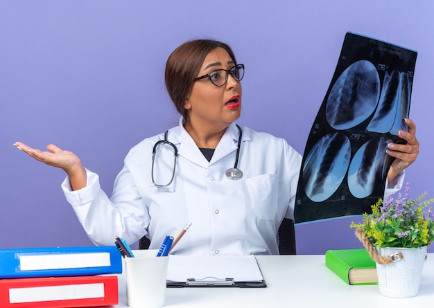 Middle age woman doctor in white coat with stethoscope wearing glasses holding x-ray looking at it confused with arm out sitting at the table over blue background