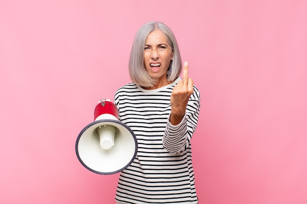Middle age woman feeling angry, annoyed, rebellious and aggressive, flipping the middle finger, fighting back with a megaphone