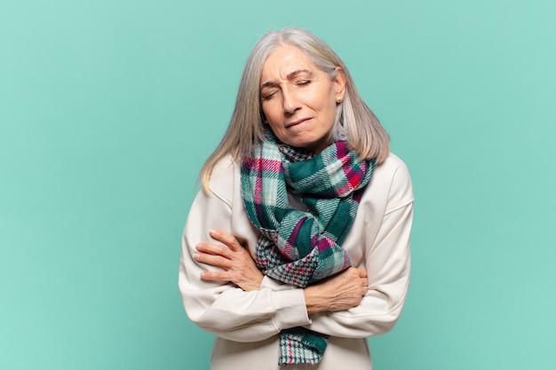 중년 여성이 불안하고 아프고 아프고 불행하며 고통스러운 복통이나 독감을 앓고 있습니다.